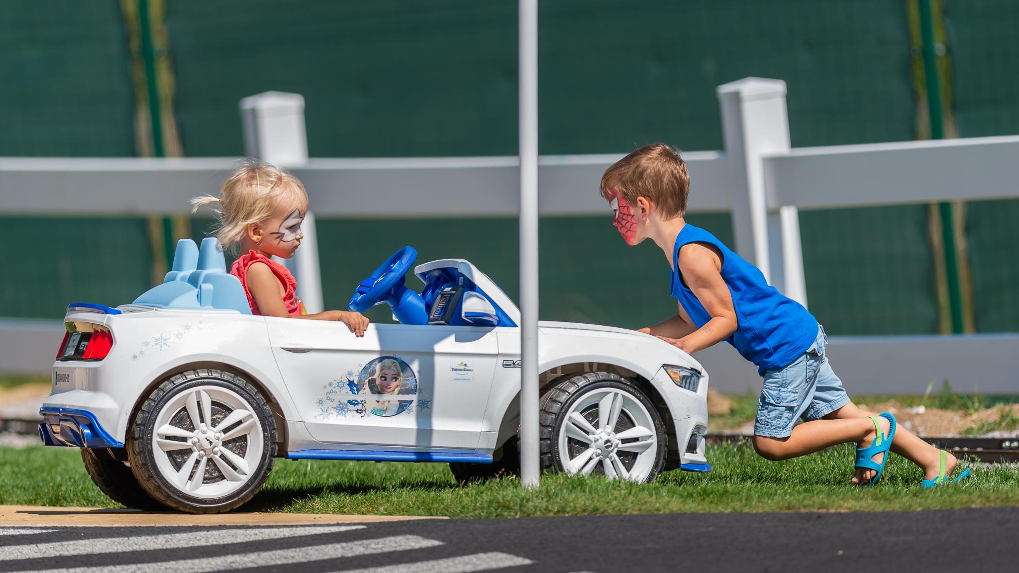 chlapec tlačiaci auto z trávy späť na detské dopravné ihrisko