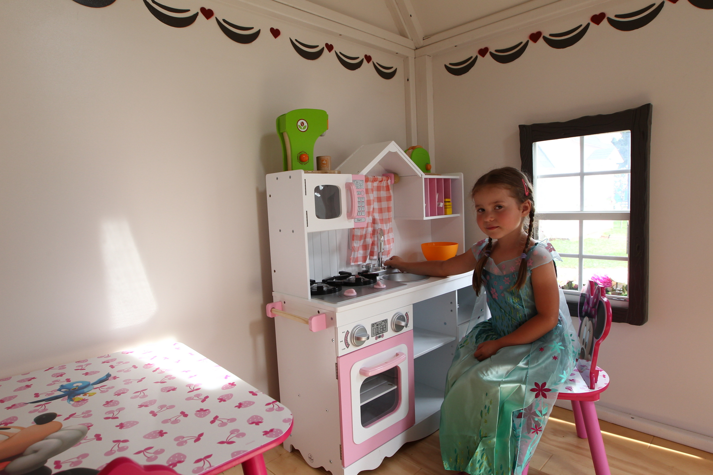 Dievčatko sediace v detskom domčeku hrajúcu sa v kuchynke