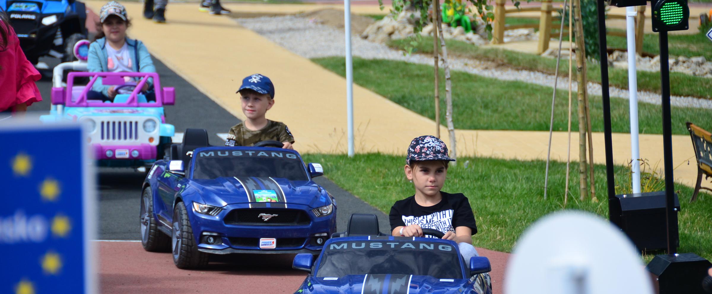 deti na ceste v Donovalkove idúce za sebou v elektrických autíčkach