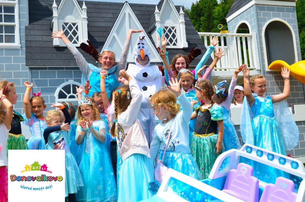 Deti v kostýmových šatách z rozprávky frozen, sa fotia spolu so snehuliakom pred zámkom v Donovalkove.